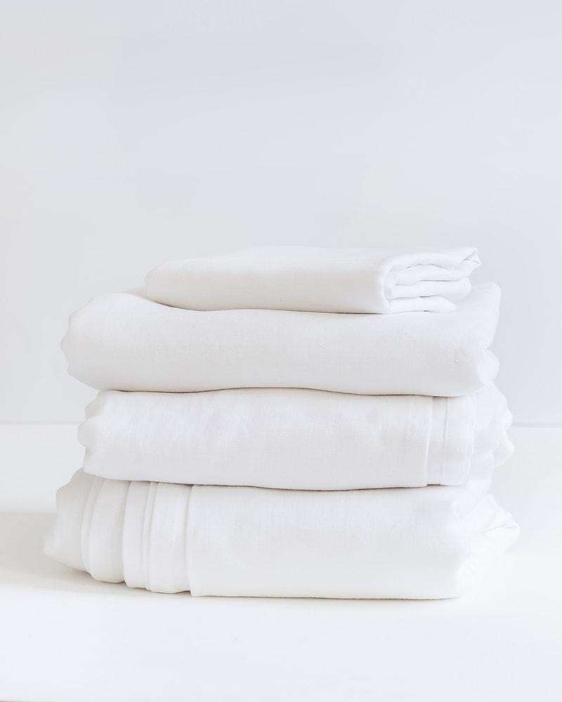 Crisp white kamma linen bedding set with duvet, flat sheet, and pillow slips, woven from Italian linen at the Mungo Mill in Plettenberg Bay, South Africa