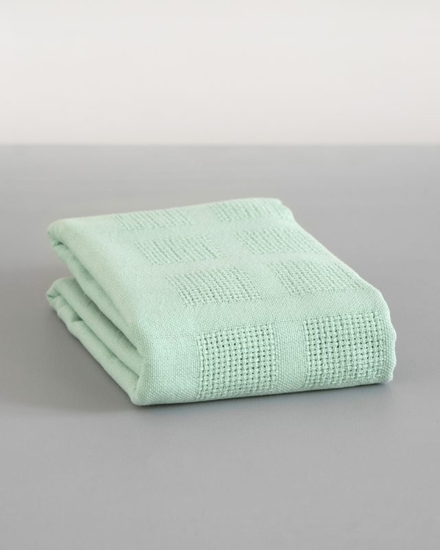 Organic cotton cot blanket in caterpillar green by Mungo woven in South Africa