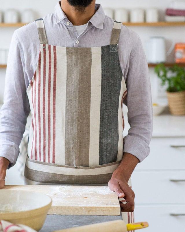 The Mungo Chef's Apron in Berry in a kitchen scene.